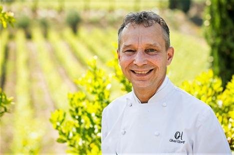 Lo che stellato Oliwer Glowig sullo sfondo delle vigne dell'azienda vinicola Poggio Le Volpi